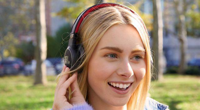 Момиче, носещо соларни слушалки JBL reflect eternal
